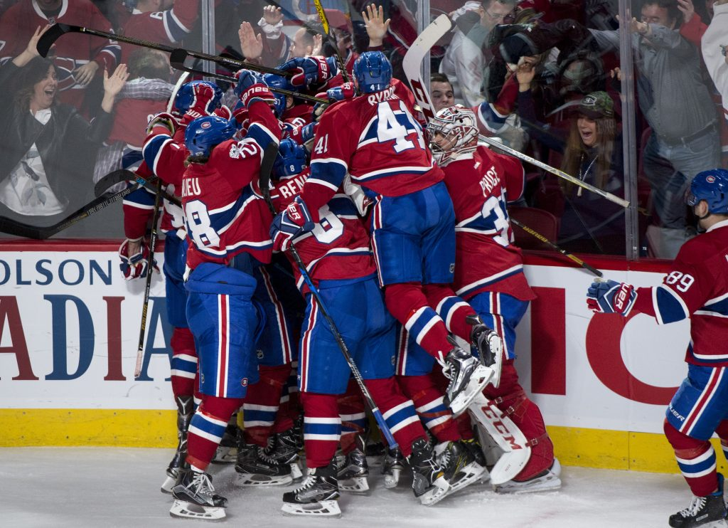 Montreal players pile on Alexander Radulov after he scores the winning goal against the New York Rangers in OT Friday night in Game 2 of their playoff series.
