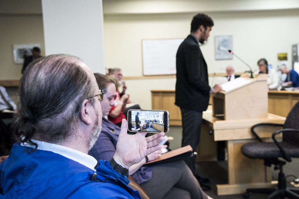 Todd Tolhurst, left, of China, president of Gun Owners of Maine, uses his phone to record the testimony of Shaman Kirkland, right, a student at the University of Southern Maine, during a hearing on a bill to allow students to carry concealed guns on college campuses. Kirkland expressed his strong objection to the proposed legislation, while Tolhurst supported it.