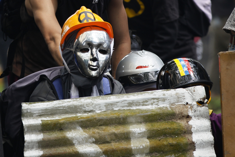 Masked demonstrators take cover during clashes with security forces at an opposition May Day march in Caracas, Venezuela, on Monday.