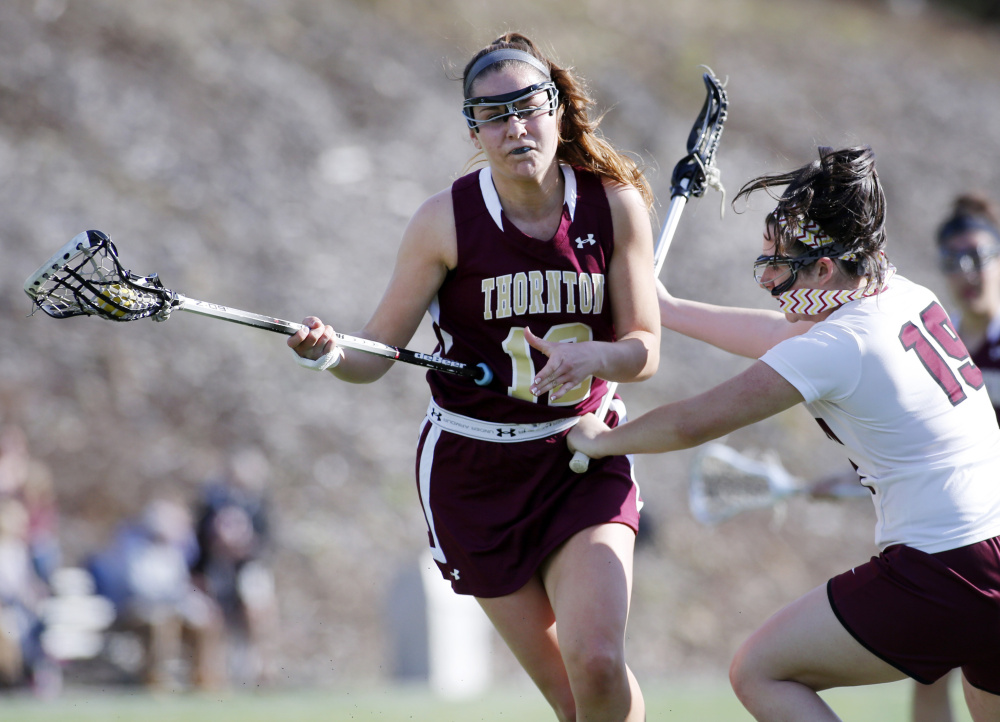 Amanda Cyr of Thornton Academy attacks the net Tuesday as Athena Pappalardo of Gorham defends during their girls' lacrosse game at Gorham High. Cyr and Pappalardo each scored two goals in Thornton's 11-6 victory.
