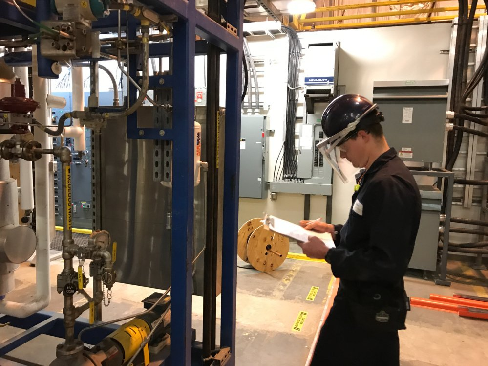 A technician takes a reading from an apparatus that turns wood waste into fuel. The University of Maine and a Massachusetts biotech firm have launched a pilot program in Old Town to prove that their technology can operate on a commercial scale.
