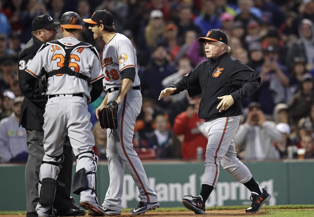 Orioles Manager Buck Showalter, right, rushes to home plate as starting pitcher Kevin Gausman argues with umpire Sam Holbrook after hitting Boston's Xander Bogaerts with a pitch in the second inning Wednesday night at Fenway Park. Gausman was ejected on the play.