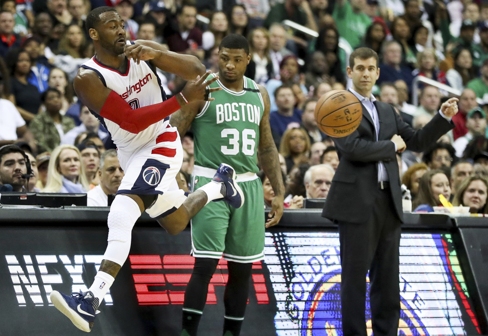 Celtics guard Marcus Smart and Coach Brad Stevens watch as Washington's John Wall  jumps out of bounds to save a loose ball during the first half Thursday night in Washington.