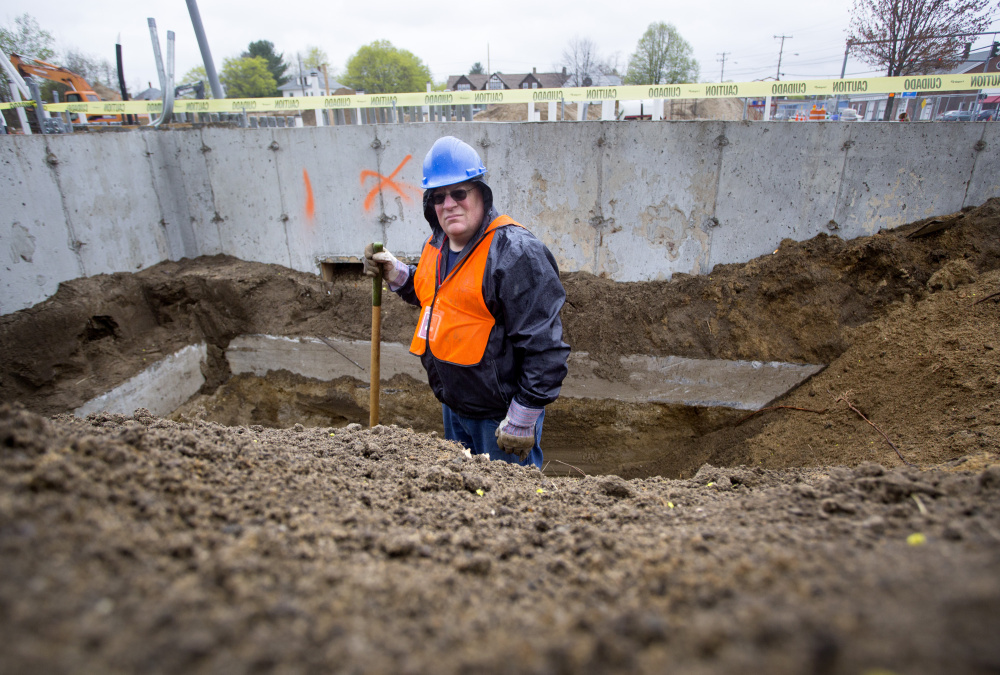 Paul Auger, a historian and teacher from Sanford, stands in a hole at a construction site on Main Street where remains from an old gravesite have been found.