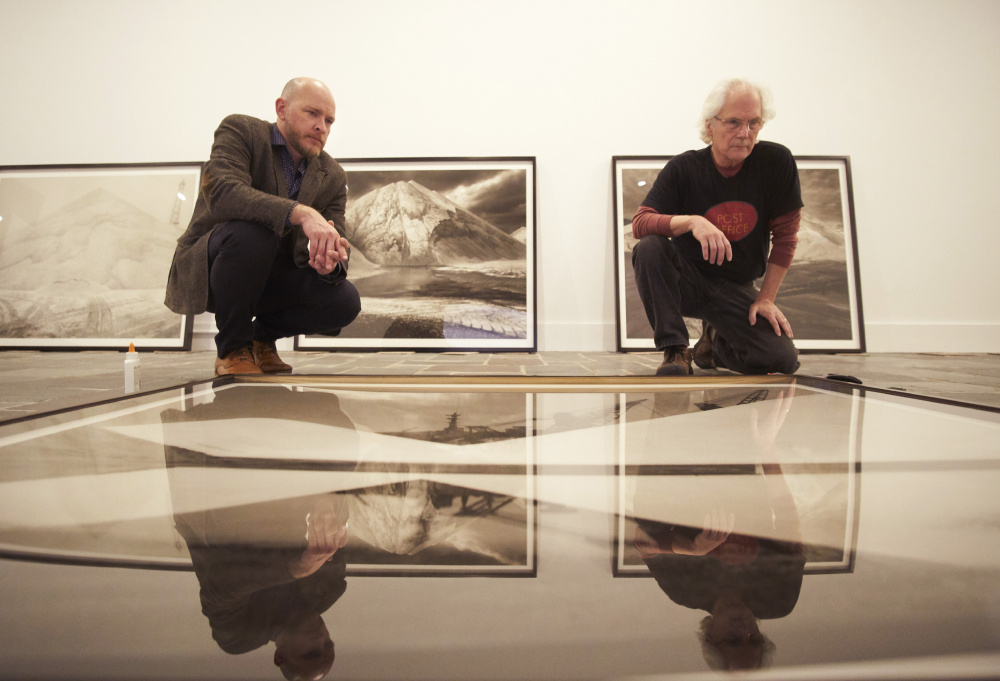 Michael Mansfield, left, the new executive director and chief curator at the Ogunquit Museum of American Art, examines a photograph with Carl Austin Hyatt in preparation for