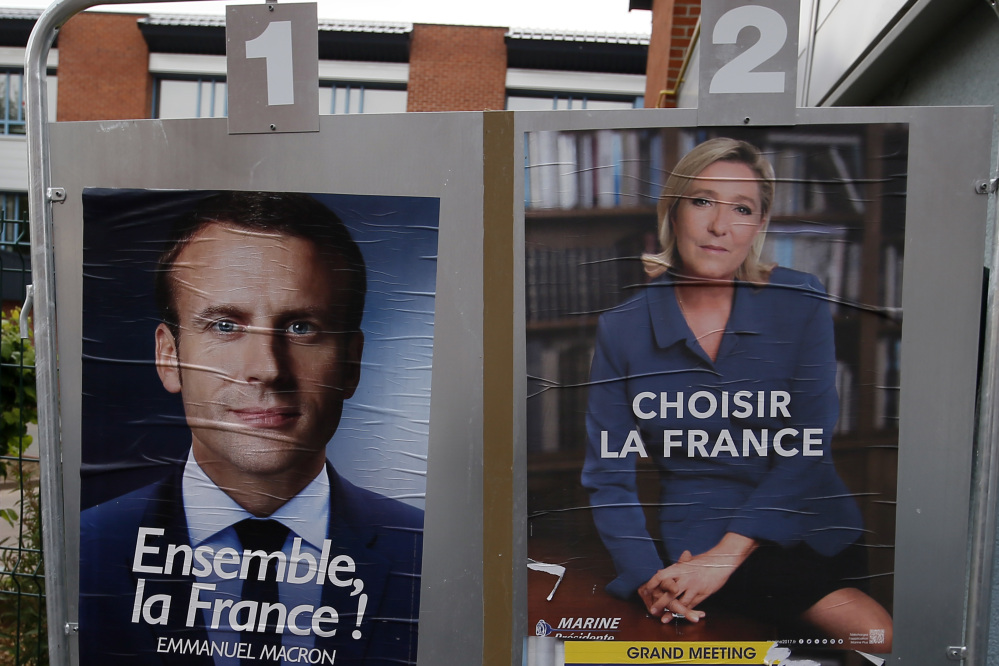 Election campaign posters for French centrist presidential candidate Emmanuel Macron and far-right candidate Marine Le Pen are displayed in front of the polling station where Le Pen will vote in Henin Beaumont, northern France.