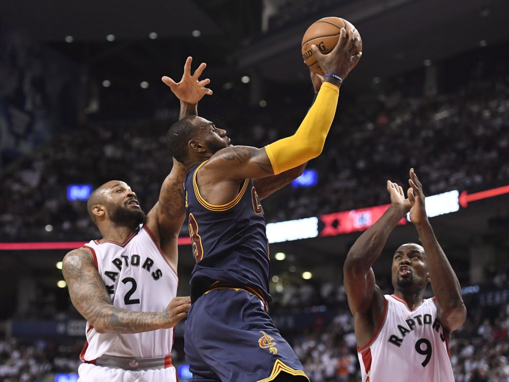 Cleveland forward LeBron James drives to the basket while being defended by Toronto's P.J. Tucker, left, and Serge Ibaka during Game 4 on Sunday in Toronto. James scored 35 points and the Cavs swept Toronto with a 109-102 win.