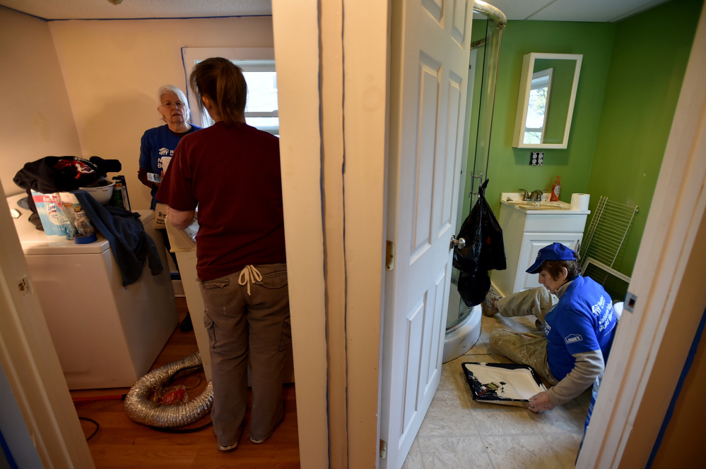 Volunteers work in the laundry room and a bathroom at 22 Water St. National Women Build Day invites women to help families build stability and independence through housing.