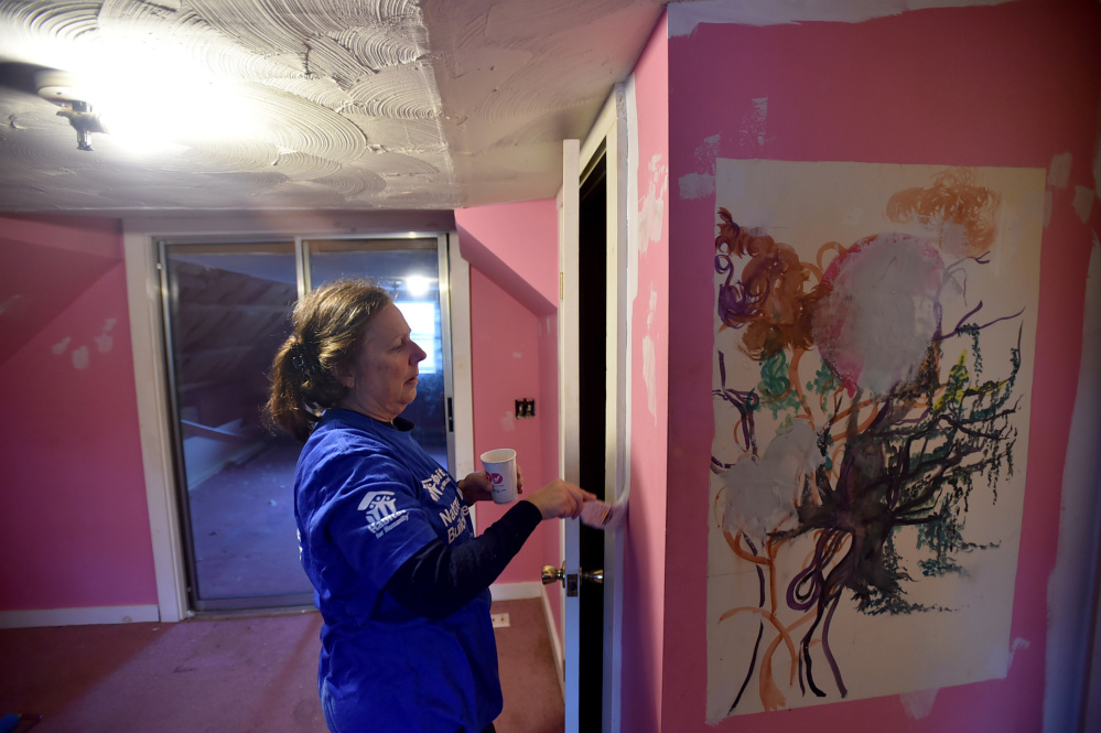 Lynn Twithell paints an upstairs bedroom Saturday while volunteering with Habitat for Humanity on National Women Build Day at 22 Water St. in Oakland.