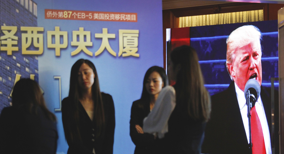 Footage of Donald Trump is shown as workers await investors during an event in Shanghai on Sunday.promoting EB-5 investment in a Kushner development.