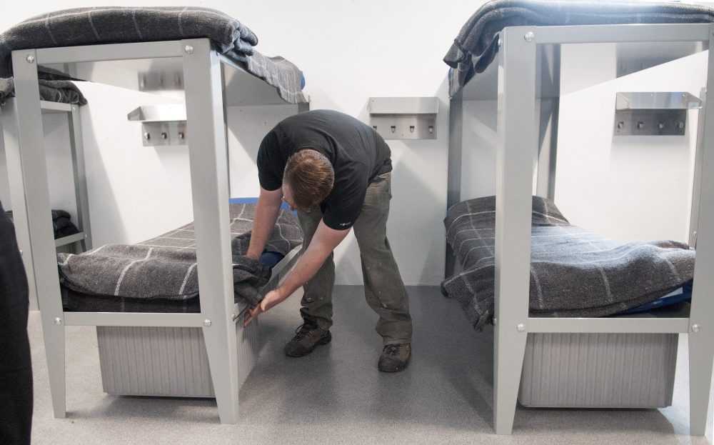 Jason Stonier, maintenance supervisor for the Kennebec County jail, puts a drawer under a bed in the new housing unit built in the jail's former indoor recreation yard.
