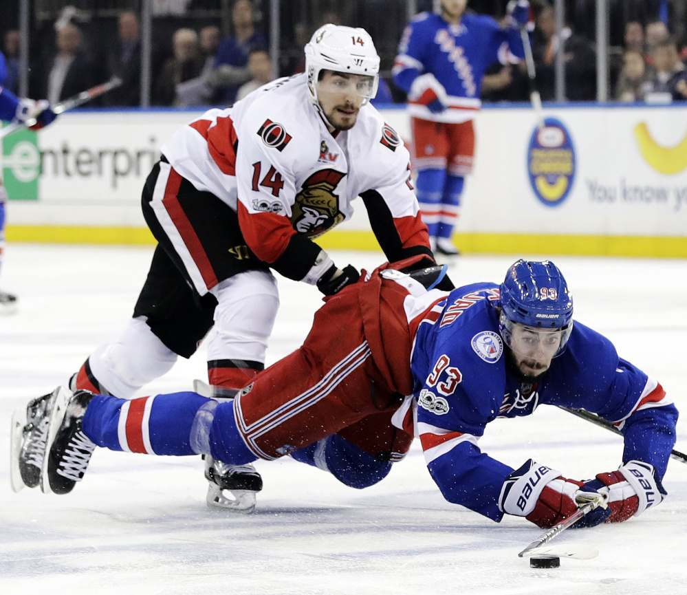 Mika Zibanejad of the Rangers goes to the ice as Ottawa's Alex Burrows pursues the puck in the second period Tuesday night in New York. Ottawa won 4-2 to take the series in six games.
