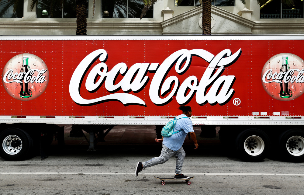 A skateboarder rides past a Coca-Cola sign on a delivery truck in Miami Beach, Fla, last fall. The company is investing in new, healthier brands, slashing expenses and offloading bottling plants around the world.