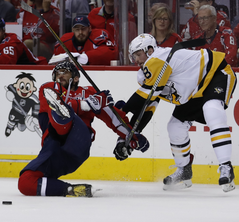 Capitals left wing Alex Ovechkin is taken to the ice by Penguins defenseman Brian Dumoulin of Biddeford during the second period of Game 7 of their playoff series Wednesday in Washington. The Penguins scored 14 seconds later.