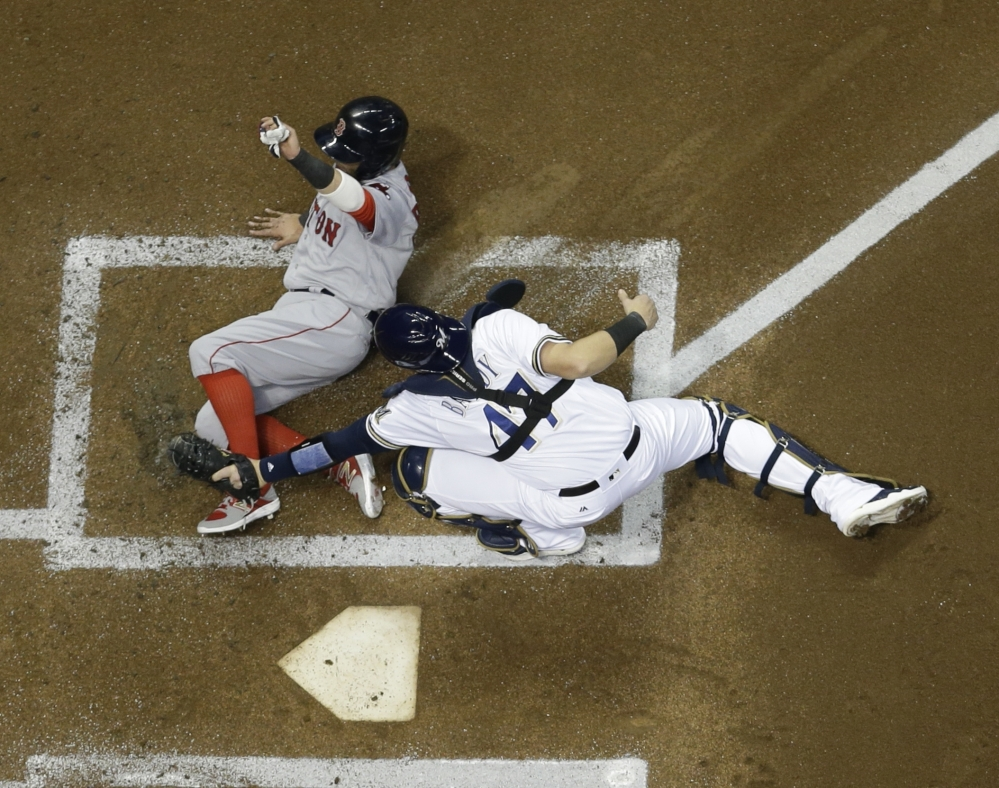 Brewers catcher Jett Bandy tags out Boston's Dustin Pedroia at home in the first inning Wednesday night in Milwaukee. Pedroia tried to score from third on a ball hit by Andrew Benintendi.