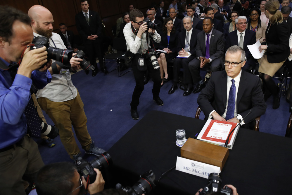 Photographers surround acting FBI Director Andrew McCabe as he takes his seat with a folder marked