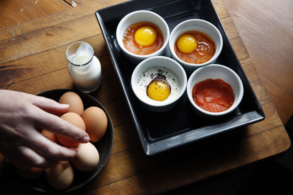 Eggs are cracked into salmon-lined ramekins. Heavy cream, dulse flakes and black pepper are added.