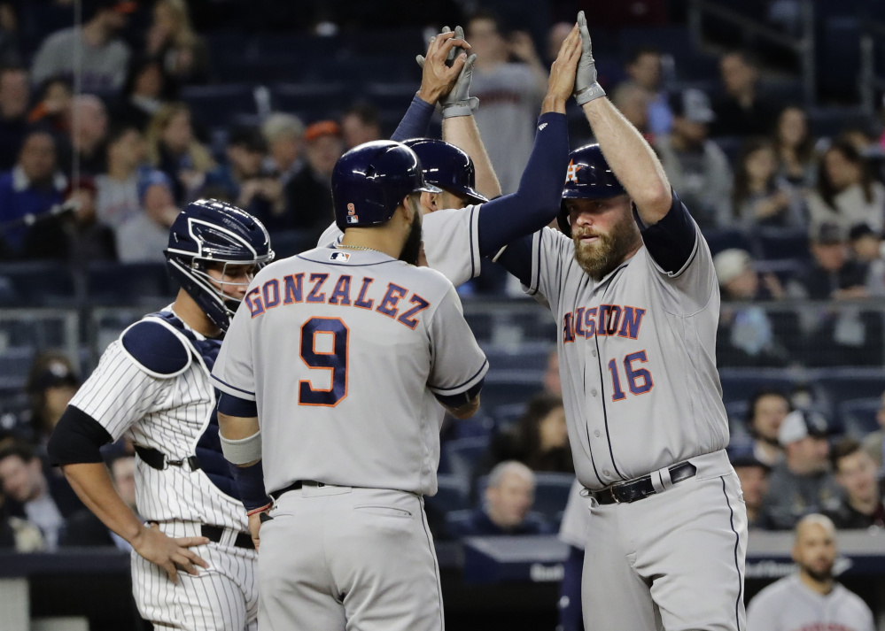 Brian McCann of the Houston Astros celebrates with Carlos Correa and Marwin Gonzalez after hitting a three-run homer in the fourth inning Friday night. Houston beat the Yankees, 5-1.