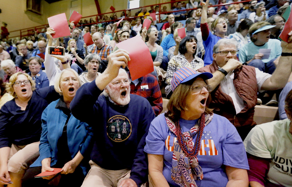 Attendees hold up their red signs to show their disapproval of Rep. Rod Blum's, R-Iowa, answer to a question during a town hall in Dubuque, Iowa, last week.