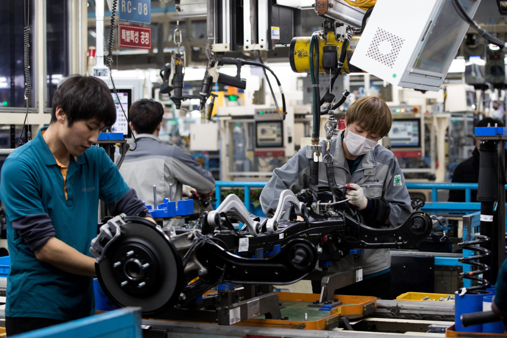 Employees assemble vehicle chassis modules on a production line at the Hyundai Mobis Co. factory in Asan, South Korea. Some South Korean companies are requiring workers to address each other by English names, and it's an uncomfortable change for many.