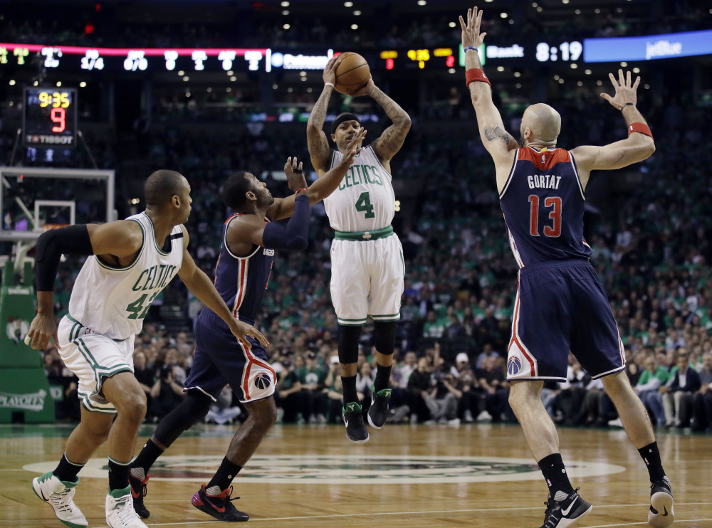 Celtics guard Isaiah Thomas shoots between Wizards guard John Wall, left, and Wizards center Marcin Gortat in the first quarter of Game 7.