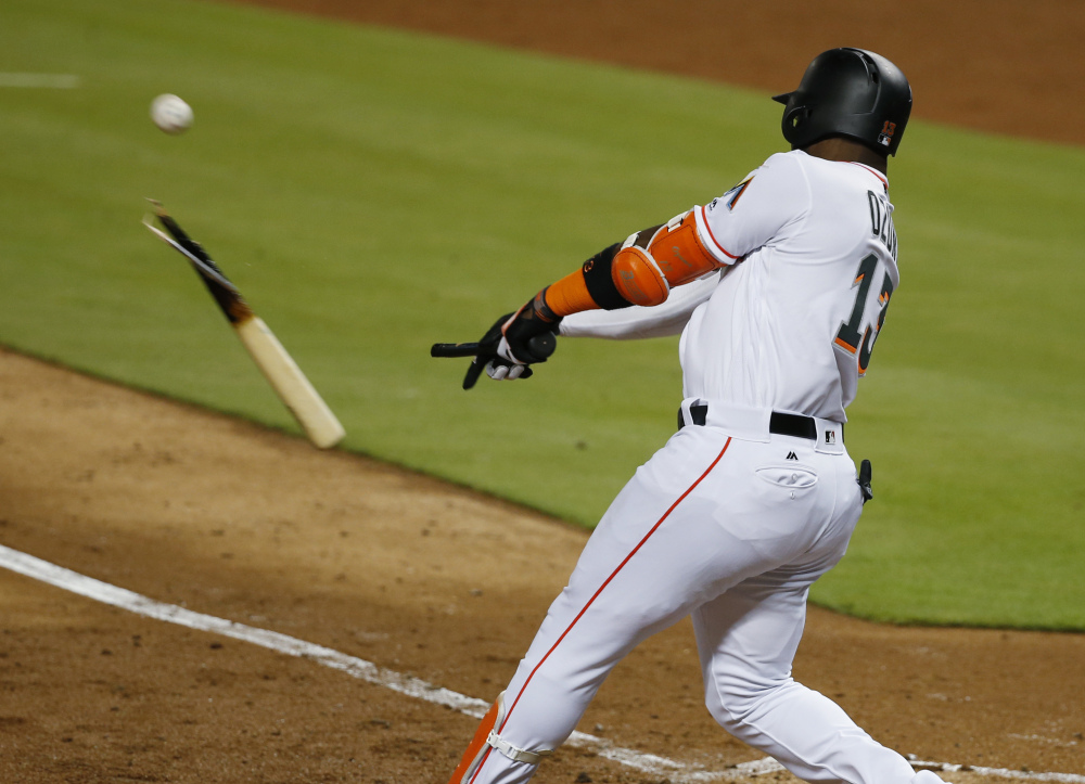 Marcell Ozuna of the Marlins breaks his bat as he hits a single during the fourth inning of Monday night's game against Houston in Miami. The Astros broke out in the sixth inning and won 7-2.