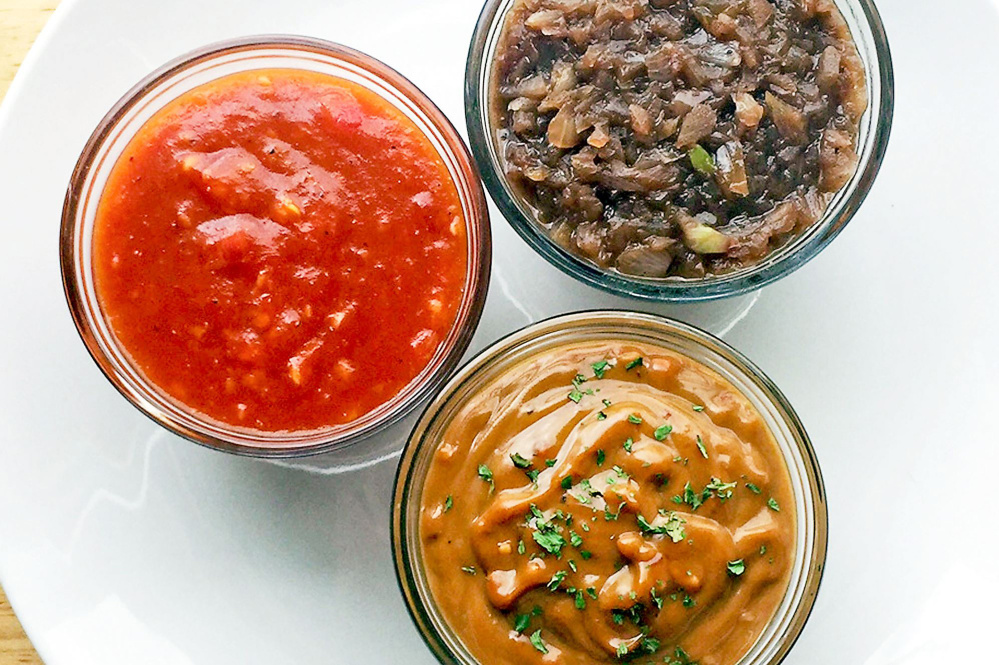 Clockwise from left, spicy mango barbecue sauce, red wine sauce and peanut sauce.