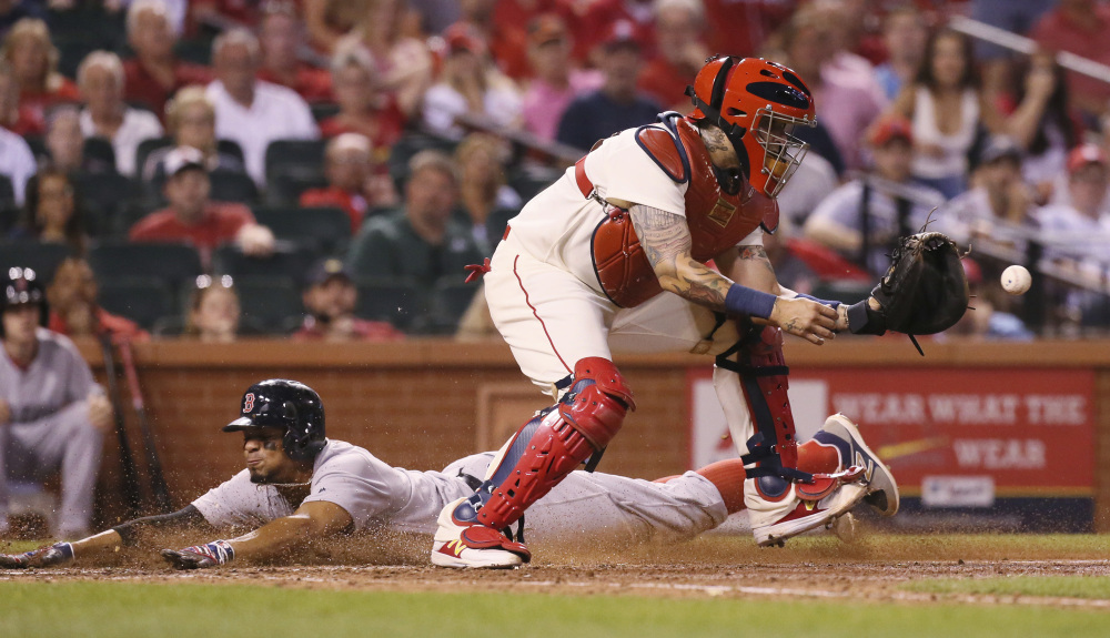Boston Red Sox shortstop Xander Bogaerts scores past St. Louis Cardinals catcher Yadier Molina on a sacrifice fly during the eighth inning Tuesday.