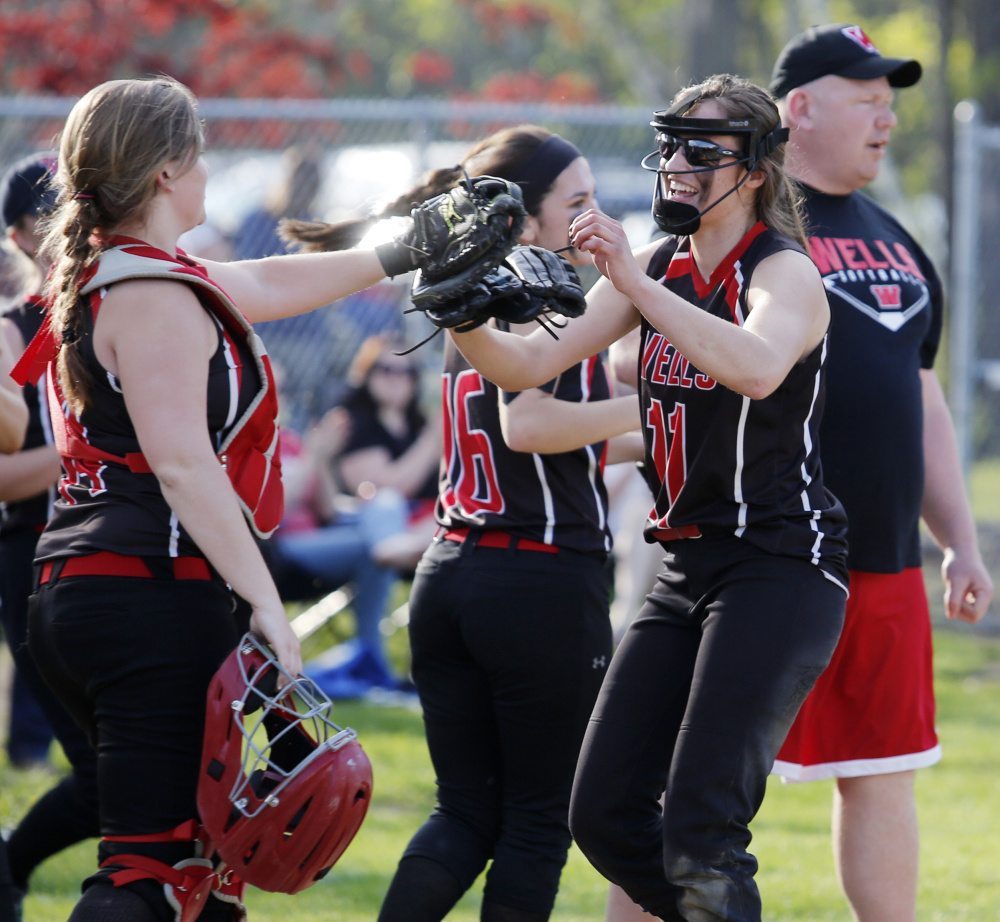 Wells pitcher Anya Chase, right, celebrates with her teammates after finishing a 1-0 victory Thursday against Western Maine Conference rival Greely.