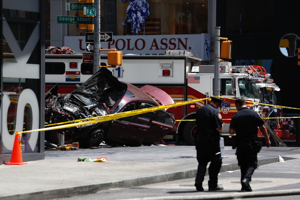 A smashed car sits on the corner of Broadway and 45th Street in New York's Times Square after plowing through a crowd of pedestrians at lunchtime on Thursday.