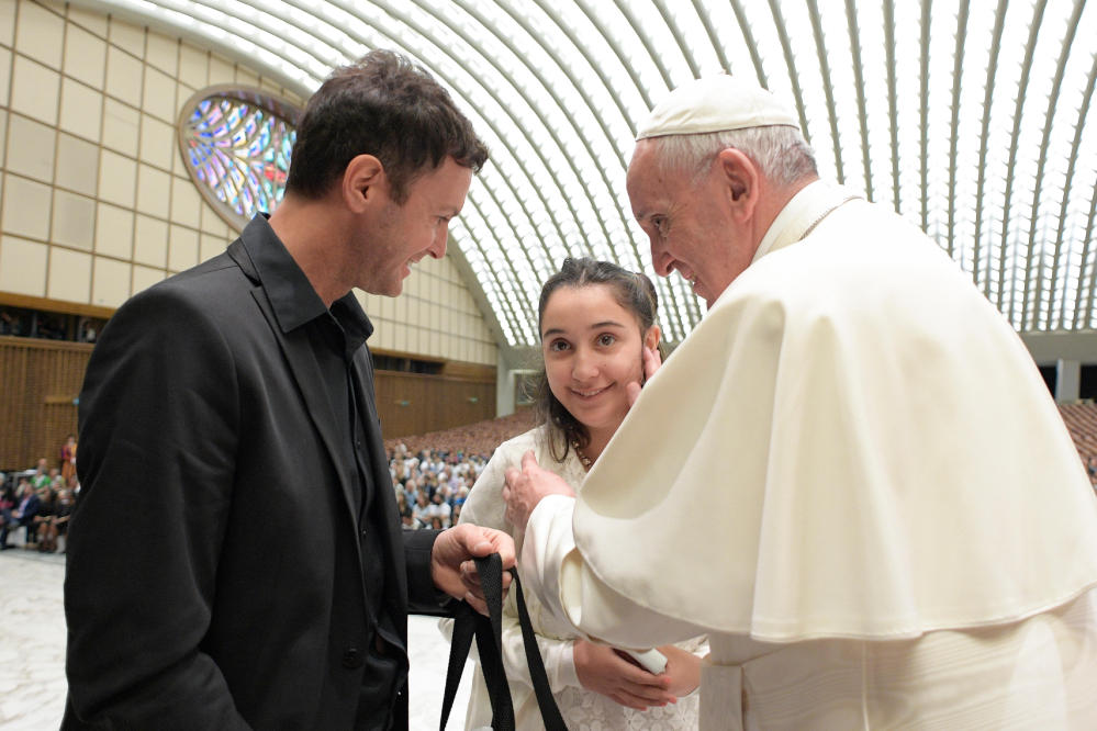 Pope Francis greets Brenda, no last name available, from Argentina, who suffers from juvenile Huntington's Disease, as she is accompanied by Argentine singer Axel during an audience with Huntington's Disease families in the Paul VI Hall at the Vatican on Thursday.