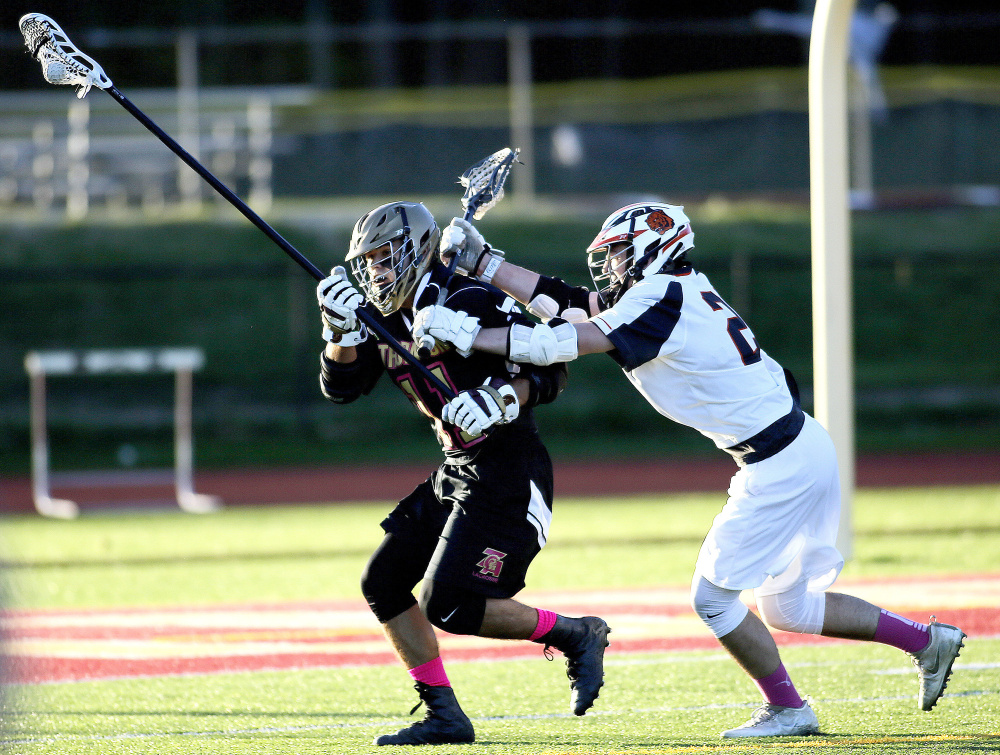 Cameron Houde of Thornton Academy attempts to evade a Biddeford defender Friday night during the first quarter of Thornton's 18-6 boys' lacrosse victory at Saco. The Trojans improved to 7-1 and dropped the Tigers to 5-4.