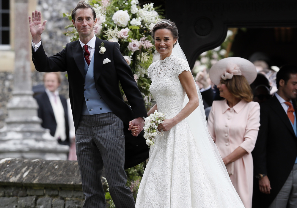 Pippa Middleton, sister of Kate, Duchess of Cambridge, and James Matthews smile for the cameras after their wedding at St. Mark's Church in Englefield, England, on Saturday.