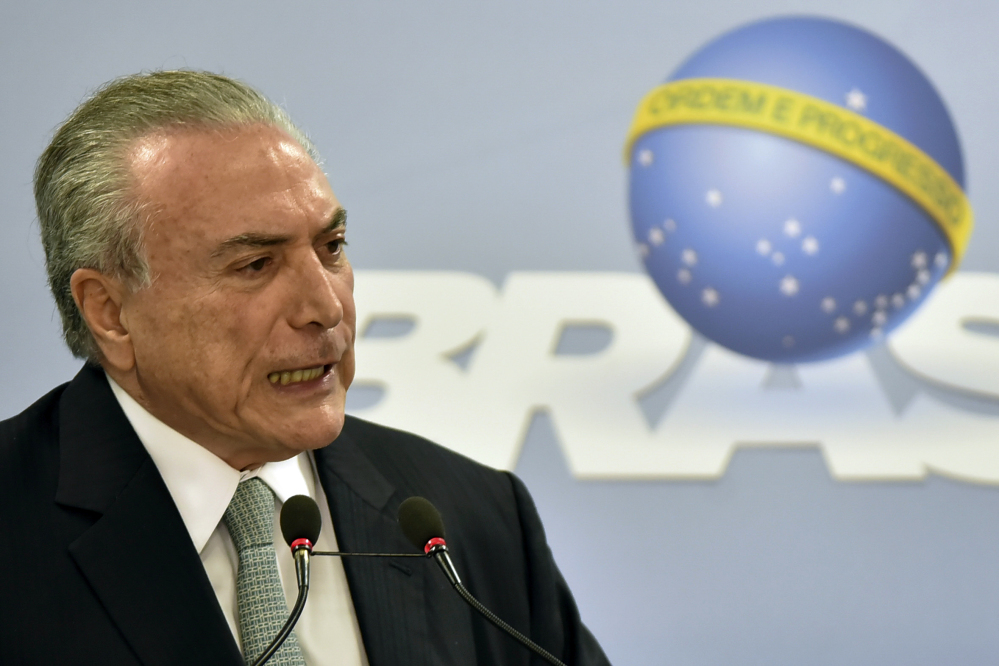 Brazil's President Michel Temer says he will fight allegations that he endorsed the paying of hush money to an ex-lawmaker jailed for corruption, during a national address at the Planalto presidential palace in Brasilia, Brazil, Thursday.