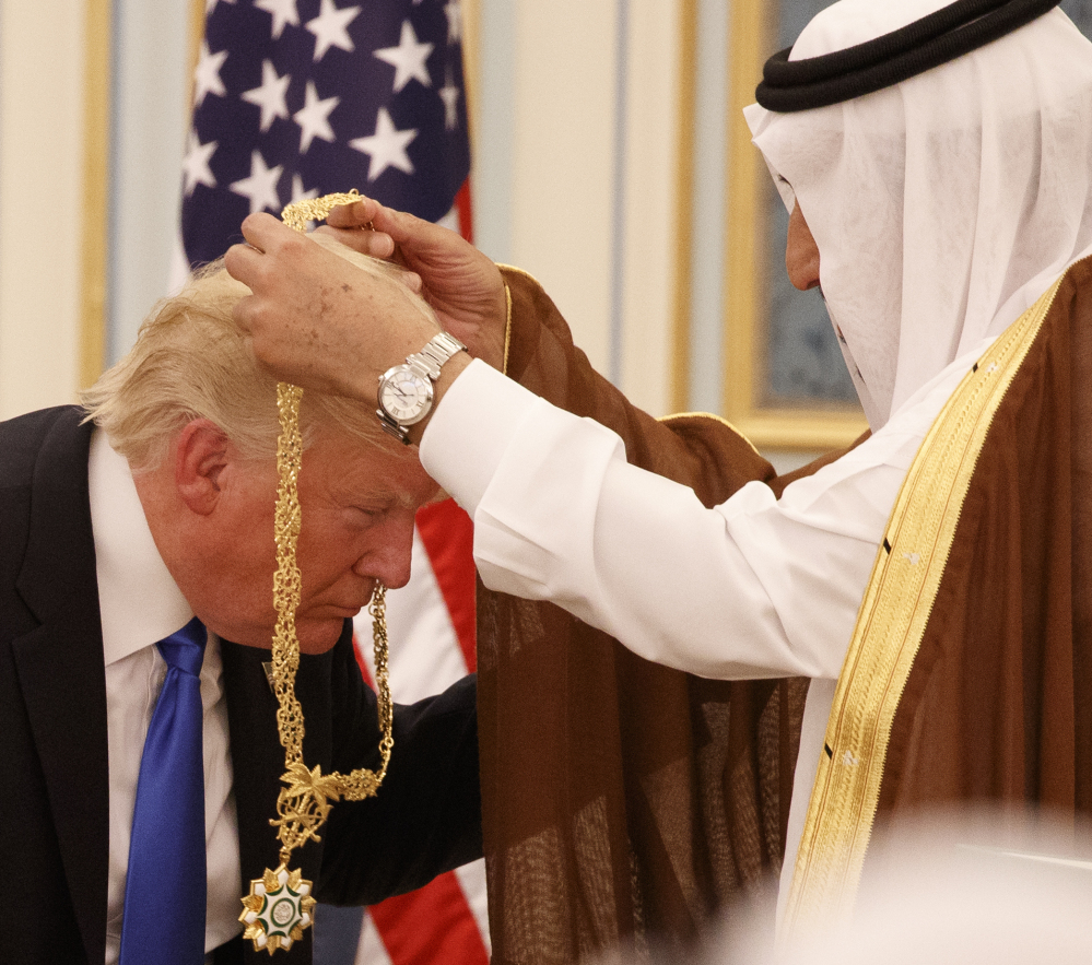 Saudi King Salman presents President Donald Trump with The Collar of Abdulaziz Al Saud Medal. At right, White House senior advisor Jared Kushner, right, enjoys the ceremony with flanked senior adviser Steve Bannon, left, and and chief economic advisor Gary Cohn.