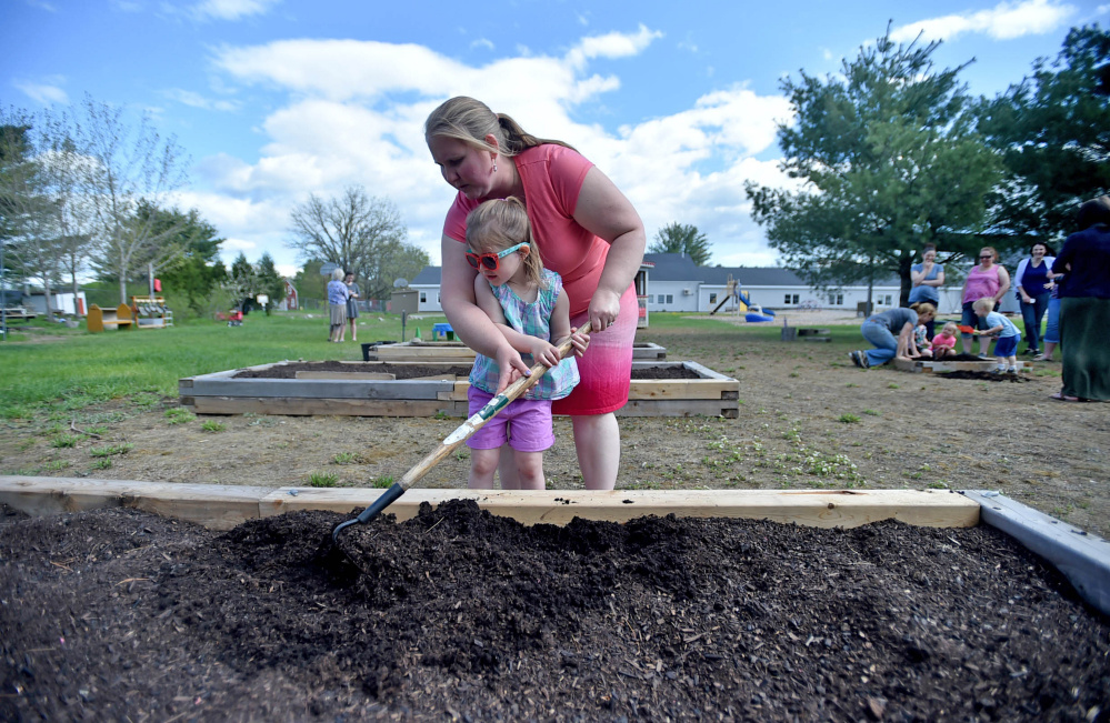 Amanda Winchenbach helps Mya Robertson, 3, prepare a soil bed at Unity Elementary School on Friday. Six staff members work with the nature-based preschool program.