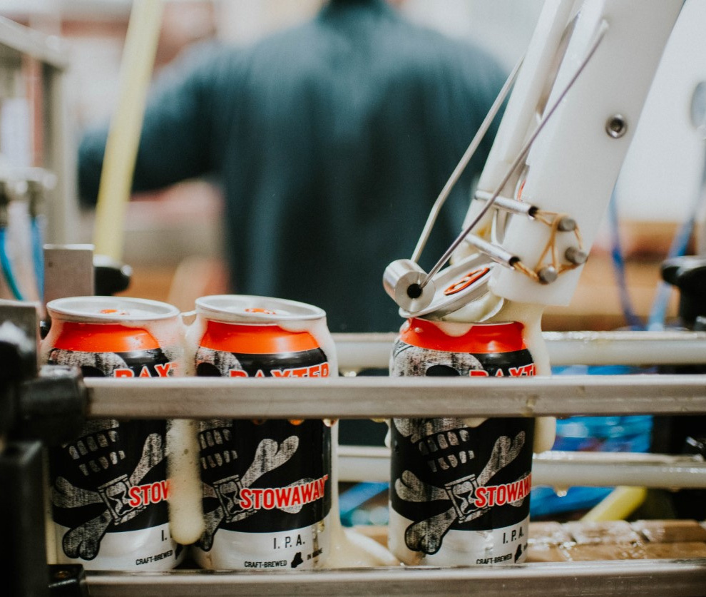 Cans of Baxter's Stowaway IPA are topped off at the company's Lewiston brewery.