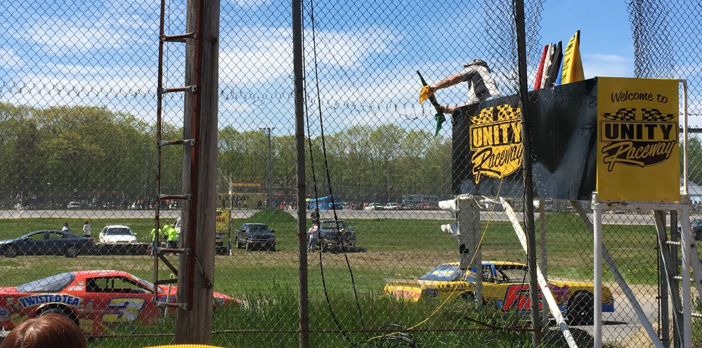 Cars race under the flagstand during a qualifying race Sunday at Unity Raceway.