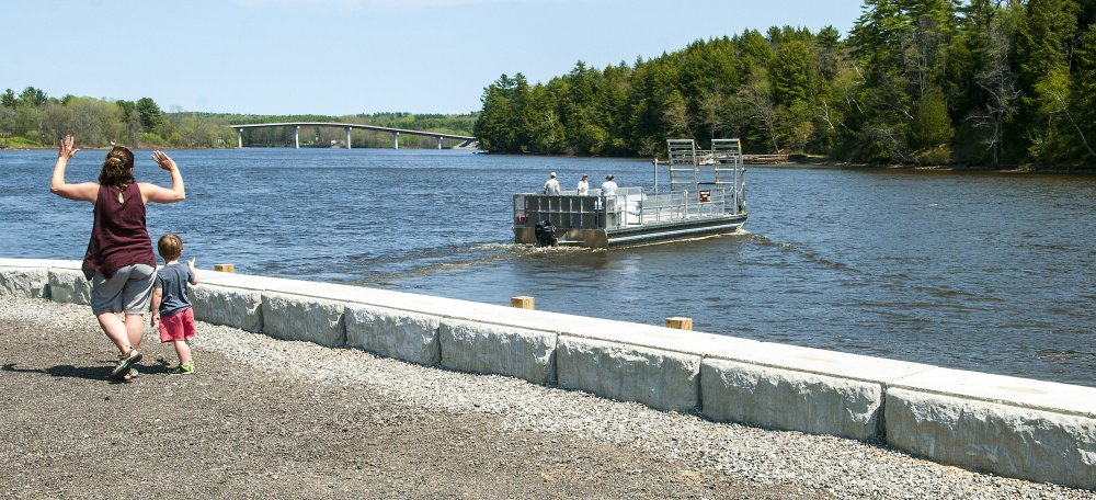 Lyman residents Liz Dunn and her son Spencer, 3, wave to the operators of the Swan Island ferry from the recently renovated boat launch area along the Kennebec River in Richmond. Dunn and Spencer had just returned from a visit to the island.