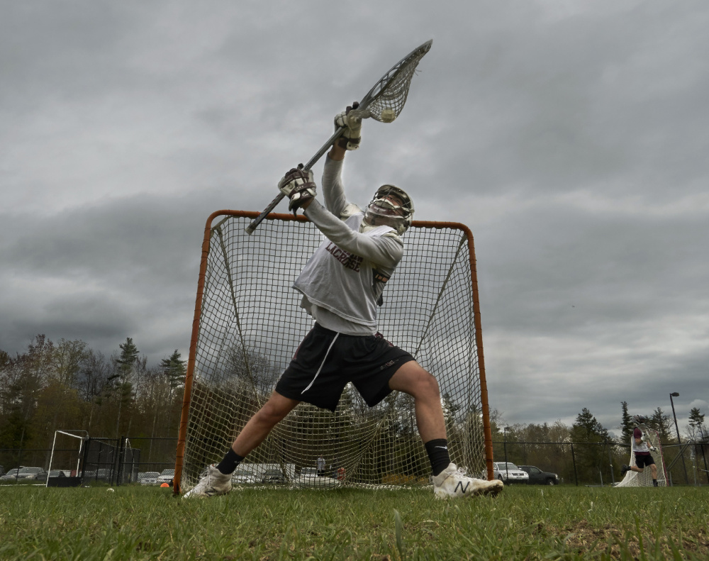 Carter Landry, Gorham High's starting goalie since his freshman year, blocks a shot during a practice last week in Gorham. Landry plans to continue playing lacrosse next year at Widener University in Chester, Pa.