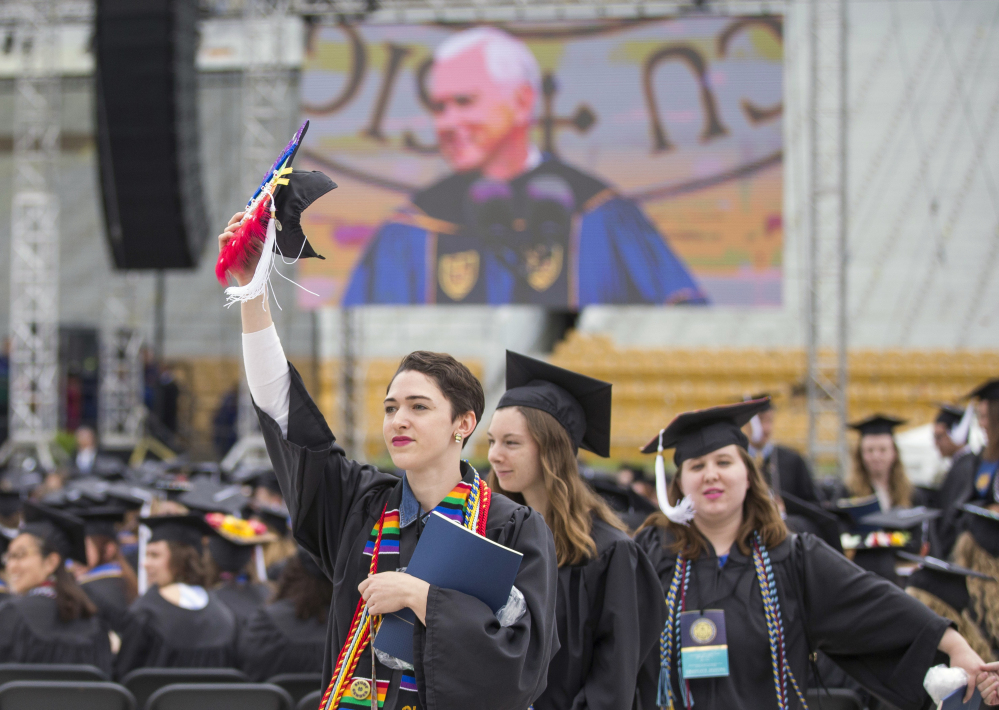 Notre Dame graduates walk out of Notre Dame Stadium in protest as Vice President Mike Pence speaks during the 2017 commencement ceremony Sunday in South Bend, Ind.