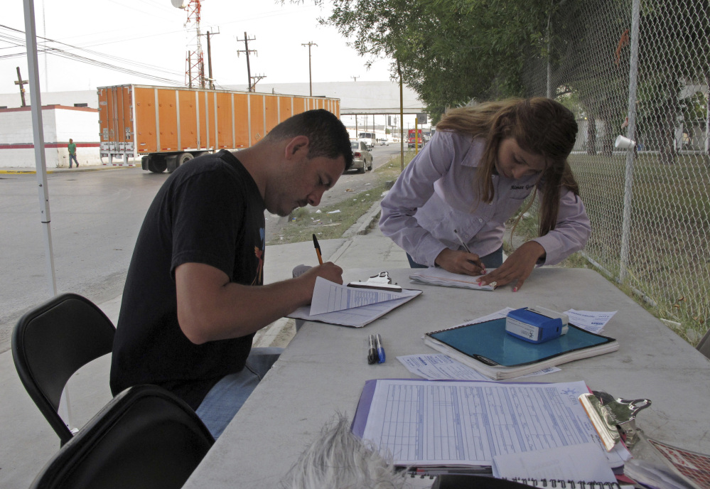 Aimee Gomez, a recruiter for assembly plants in Reynosa, Mexico, helps Juan Luis Alvarado de la Rosa fill out a job application at an industrial park across the border from McAllen, Texas. President Trump has said NAFTA was