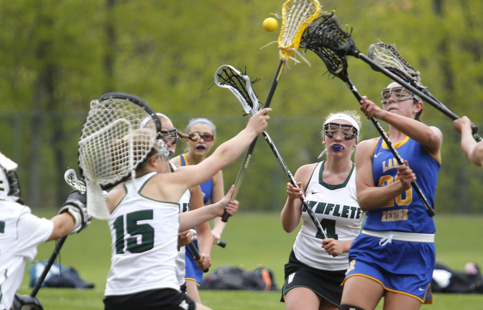 Lauren Jakobs of Lake Region tries to get off a shot as Waynflete defenders close in during the first half of Monday's girls' lacrosse game in Portland. Jakobs had two goals, but Lake Region lost in double overtime.