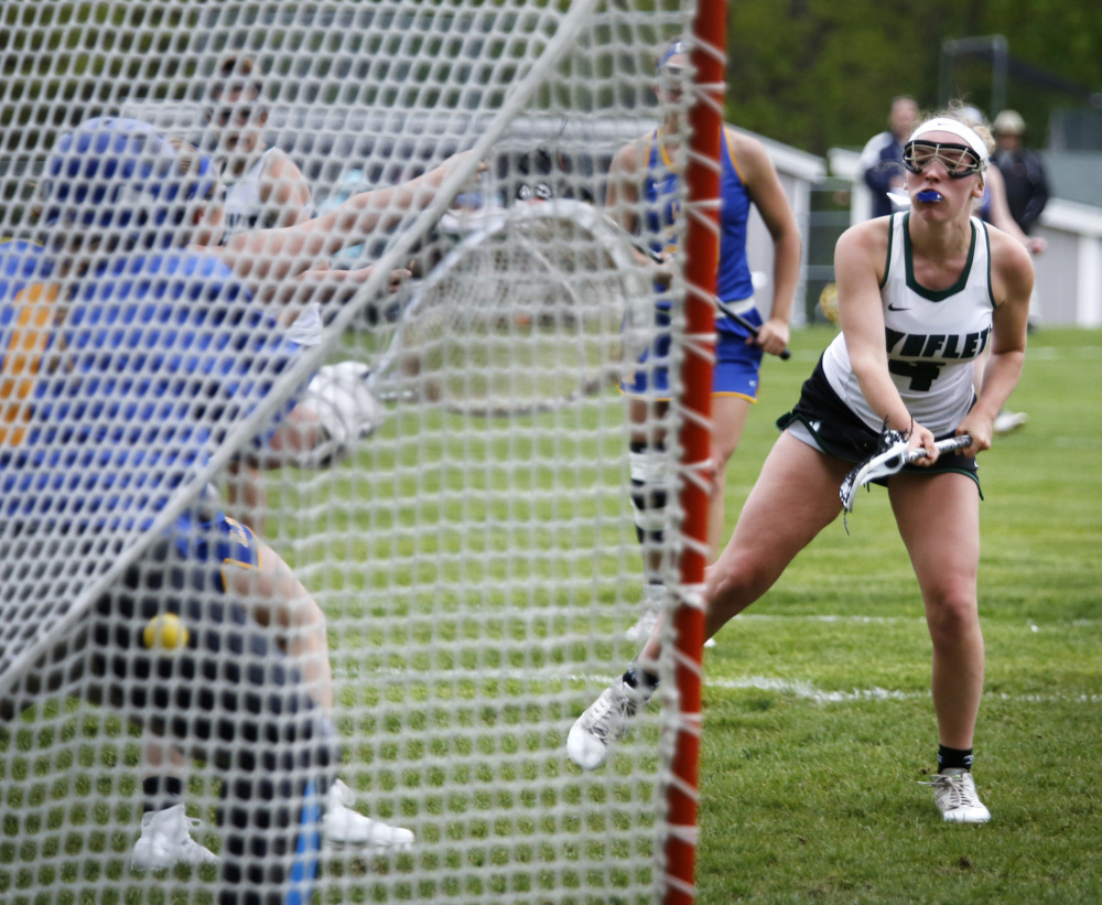 Laura Baginski of Waynflete watches as her shot gets past goalie Maddie Nelson of Lake Region in the second half. Baginski finished with three goals, including the winner in the second overtime.