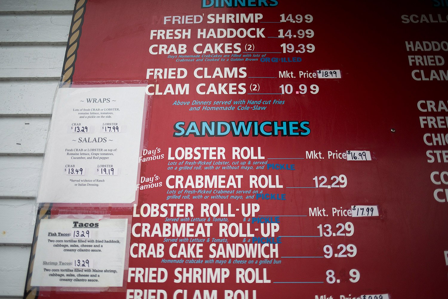 The menu at day s crabmeat lobster in yarmouth on thursday shows its record price of 16 99 for a lobster roll sandy owens the owner expects the price