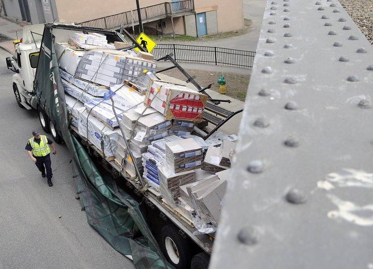 State Trooper Shawn Porter examines a tractor-trailer that struck the trestle on May 5, 2015 on Water Street in Augusta. The accident that occurred at 8:45 a.m. ripped apart the trailer but no injuries were reported, according to Augusta Police Lt. Kevin Lully. Traffic was down to one lane as the contents of the damaged trailer were moved to enable the truck to be towed away. Augusta and State Police are investigating the accident, according to Lully.