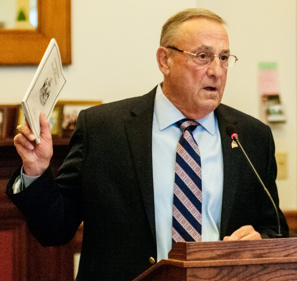 Gov. Paul LePage holds up a copy of the state Constitution as he testifies before the Legislature's Judiciary Committee on Tuesday in the State House in Augusta. LePage testified against a bill that would strip the governor of the power to approve staff pay raises within the Attorney General's Office.