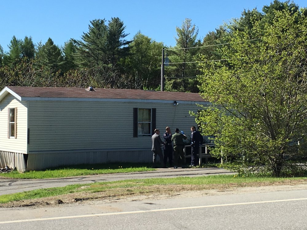Authorities gather Saturday morning outside the Belgrade mobile home where one man was killed and one person was injured in an officer-involved shooting the previous night.