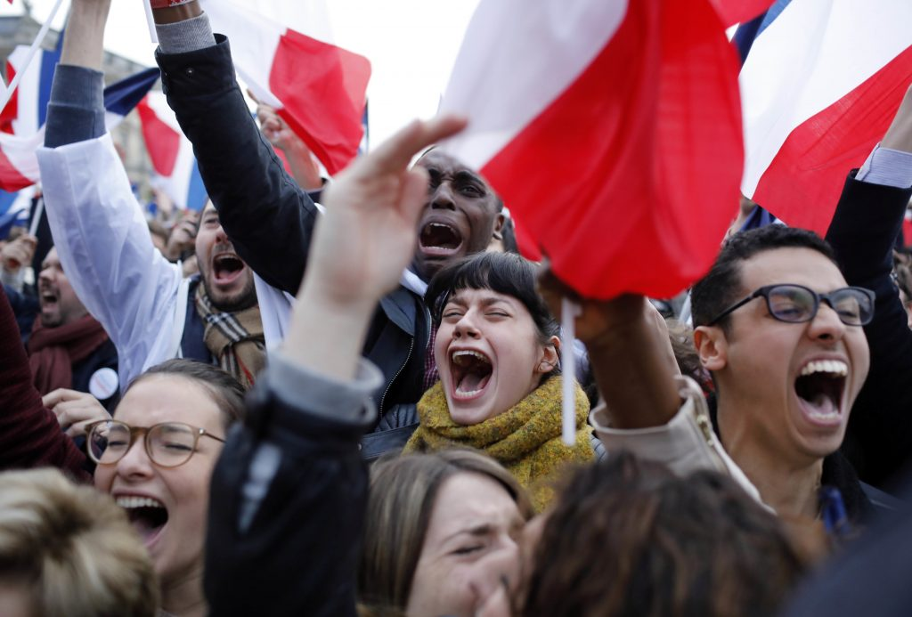 Supporters of Emmanuel Macron react outside the Louvre museum in Paris on Sunday.