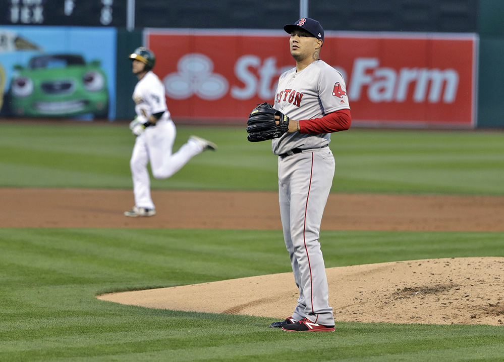 A stunned Hector Velazquez stands near the mound after Oakland Athletics' Jed Lowrie, left, hit a a two-run home run during the first inning of Thursday's game in  Oakland.